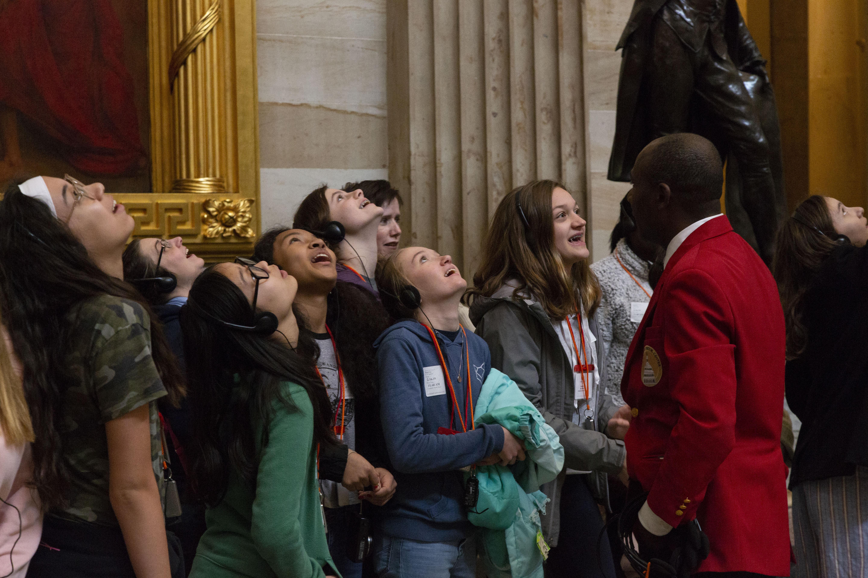 students looking up at art